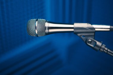 microphone on stand, blue background with acoustic foam wall in studio