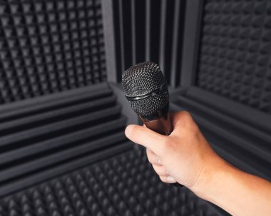 golden microphone in hand, gray background with acoustic foam in studio
