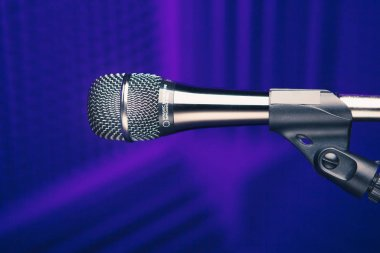 microphone on stand, purple background with acoustic foam wall in studio
