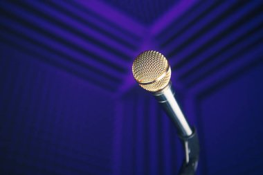golden microphone on stand, purple background with acoustic foam in studio