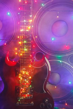 electric guitar with festive Christmas lights and music speakers in smoke