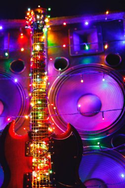 electric guitar with festive Christmas lights and music speakers