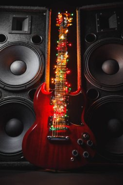 abstract guitar with festive Christmas lights and music speakers