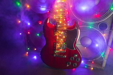 abstract guitar with festive Christmas lights and music speakers in smoke