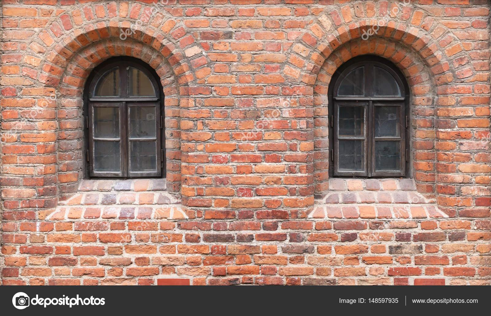 En una pared de ladrillo rojo del castillo medieval hay dos ...