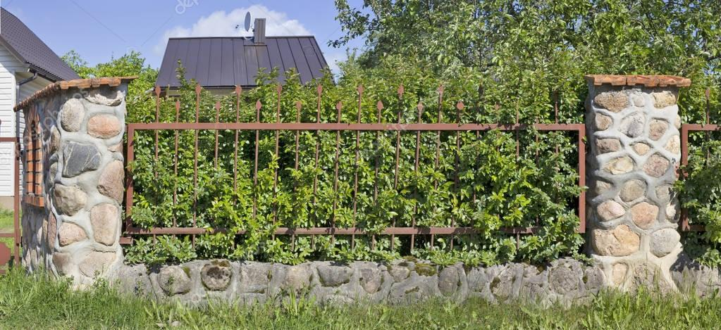 Fragment of the village fence. Made of whole granite stones and