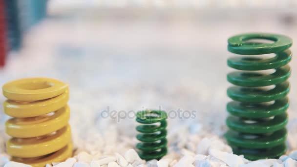 Barevné kovové pružiny stát na bílé mramorové makadam kameny na displeji