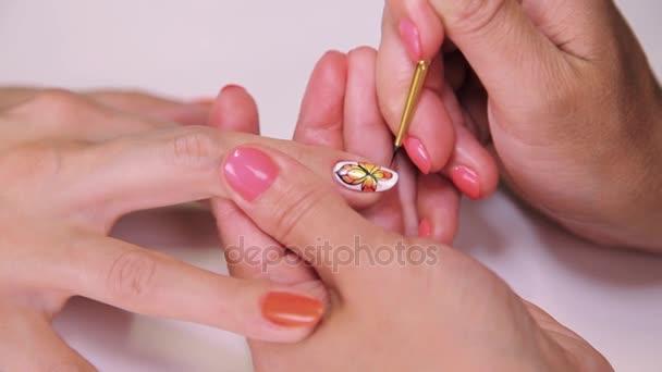 Žena kosmetička Malování nehtů polský oranžový motýl v kosmetickém salonu