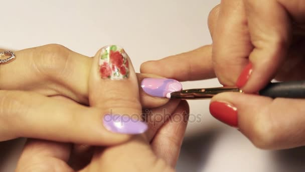 Manikérka rukou naneste lak růžové prst na bílém stole v kosmetickém salonu