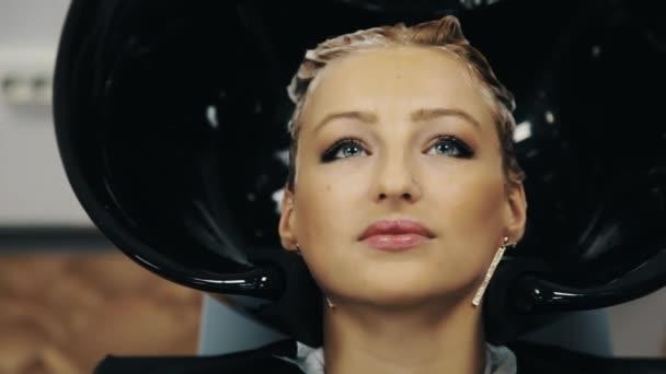 Coiffeur a guanti lavaggio dei capelli tinti biondo della donna sopra lavandino nel salone di bellezza