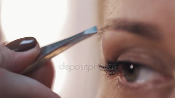 Beautician in medical mask pluck woman eyebrows with tweezers in beauty saloon