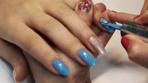Kosmetika manikúra relace, ženské ručně malované nehty modré polsky