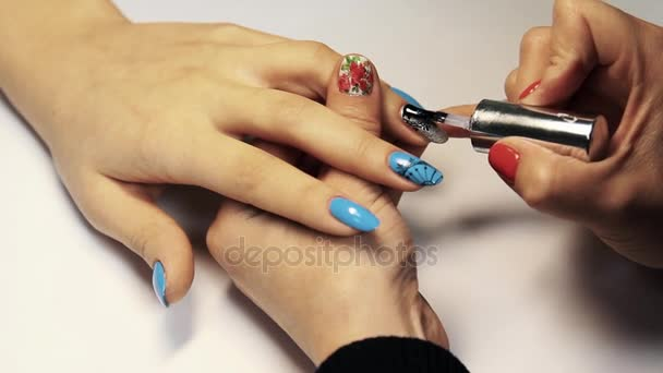 Beauty shop manicure session, woman hand put trasparent polish on painted nails