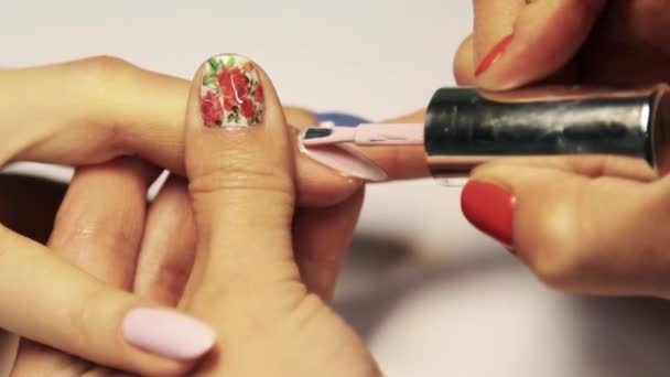 Beauty shop manicure session, woman hand painting finger nails pink polish