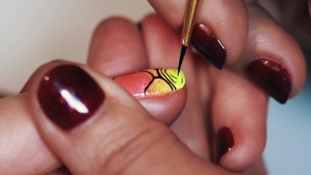 Manikérka ženské ruky kreslit abstraktní vzor barevný lak na nehty salon krásy