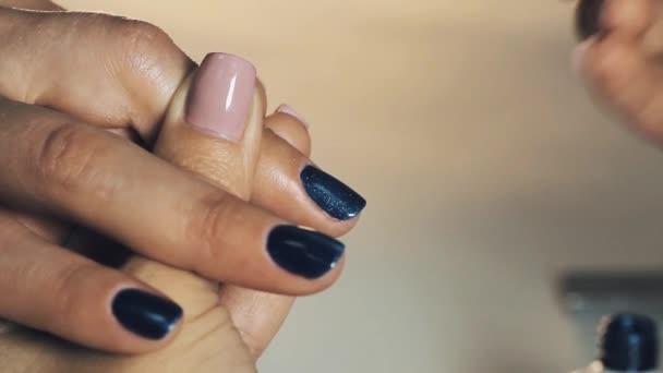 Žena manikérka ruka uvedení tmavě modrý magnetický lak na nehty v kosmetickém salonu