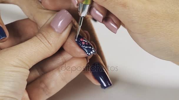 Žena manikérka ruka kreslení bílé tečky na modrý lak na nehty v salonu krásy