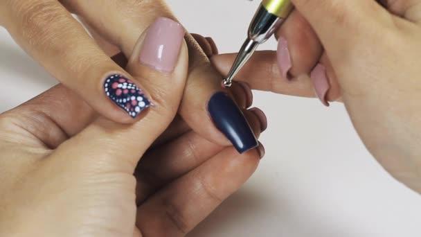 Žena manikérka ruka kreslení růžové tečky na modrý lak na nehty v kosmetickém salonu