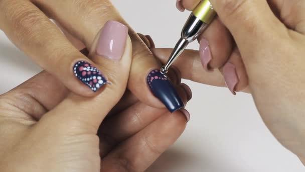 Ženské manikérka rukou nasadil modrý lak na nehty v kosmetickém obchodě bílé tečky