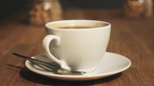 Bílý hrnek kouřící horké kávy nápoj na talíř dřevěný stůl