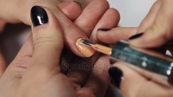 Female manicurist hand put beige polish on nails in beauty saloon white table