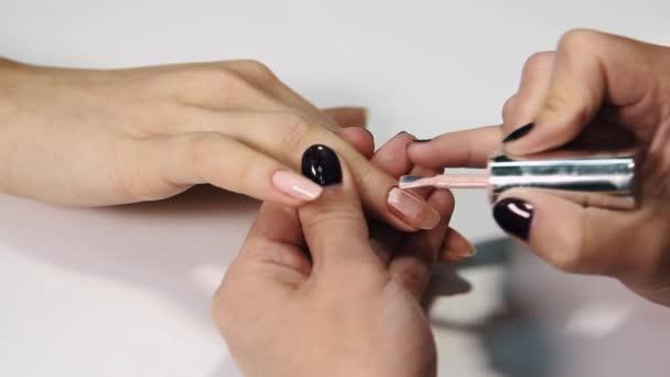Ženské kosmetička ruku aplikovat tělové polské na hřebíky v beauty salónu bílý stůl