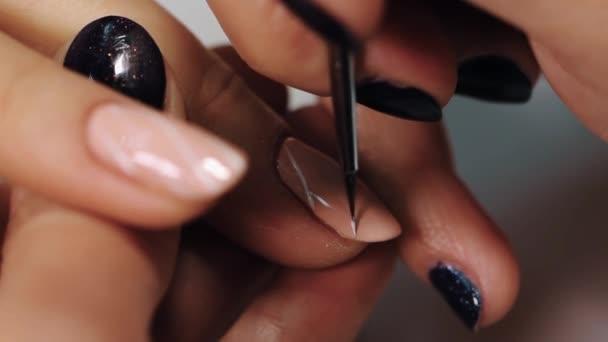 Ženské manikérka ručně nakreslete bílé pruhy na tělové nehty v salonu krásy