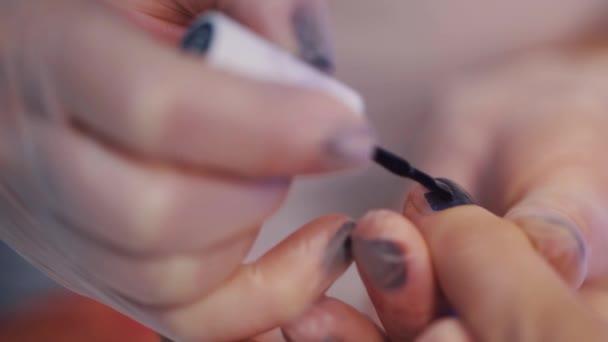 Žena v chirurgické rukavice udělat manikúru aplikovat lak na nehty na prstech, kosmetika