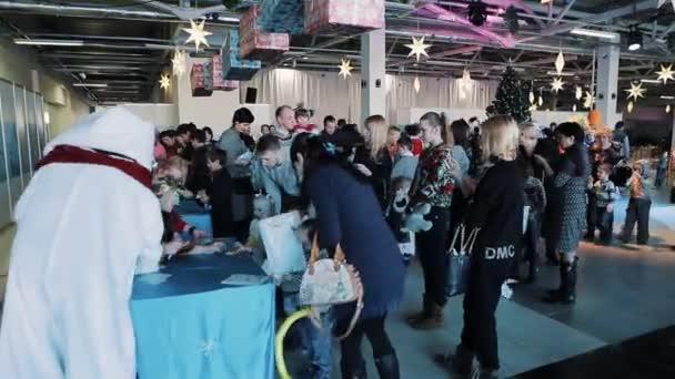 a79becc349 San Pietroburgo, Russia - 20 dicembre 2016: Folla di bambini e genitori  ottenere borse con i regali di Natale da attori in costumi– filmato stock