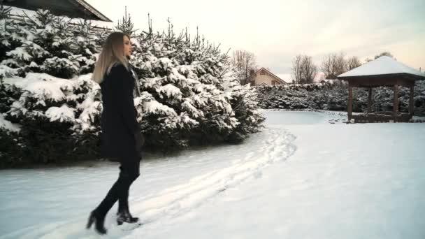 Blond žena v černém kabátě procházky k altánku na sněhu zahrnuty předměstského dvorku