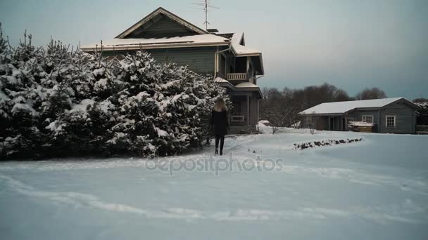 Blond žena v černém kabátě chodit do domu verandou na sněhem pokryté předměstského dvorku