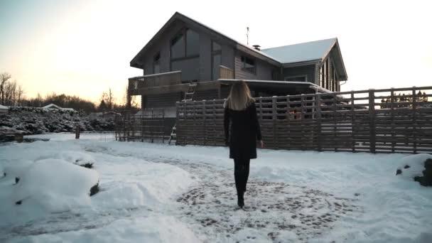 Blond žena v černém kabátě, chůze na stáž na sníh zahrnuty předměstského dvorku