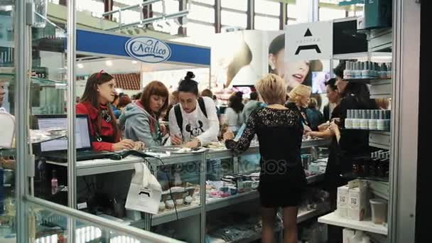 SAINT PETERSBURG, RUSSIA - SEPTEMBER 24, 2016: Women gathered around showcase with nail polish at cosmetic exposition