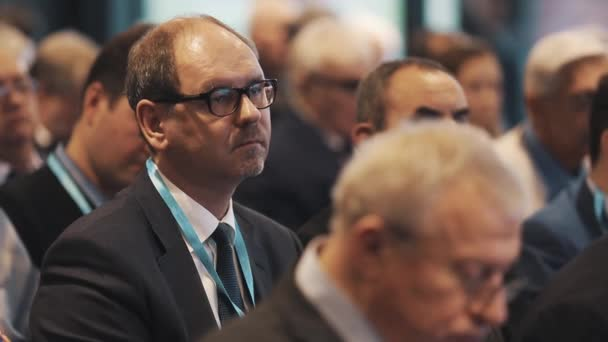 Petrohrad, Rusko - 7. listopadu 2015: Muž v brýlích a oblek sedí v hale davem lidí na obchodní konferenci