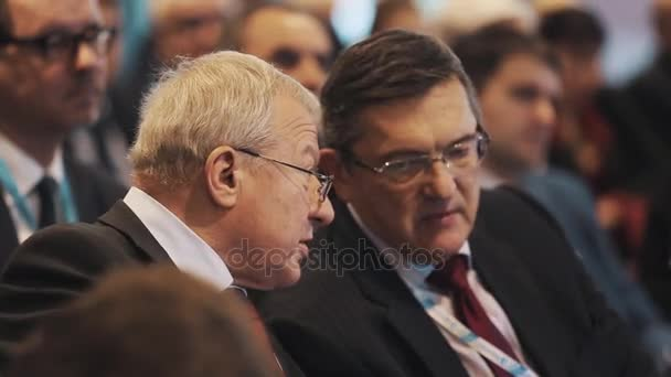 SAINT PETERSBURG, RUSSIA - NOVEMBER 7, 2015: Men in glasses and suit talking in people crowd hall at business convention
