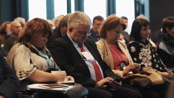 SAINT PETERSBURG, RUSSIA - NOVEMBER 7, 2015: Row of people in suits sitting in people crowd hall at business conference