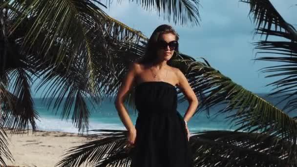 junges Mädchen in schwarzem Kleid tanzt und singt unter Palmenblättern am Meeresufer
