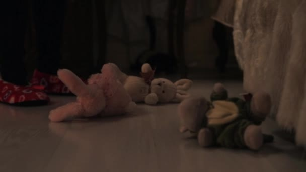 Legs in red slippers kicking around plush animal toys on children room floor