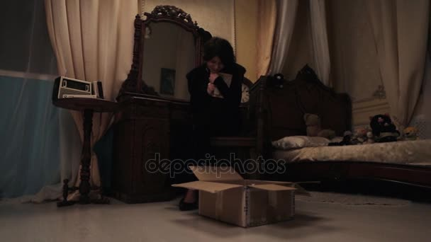 Woman In Black Crying In Bedroom Over Cardboard Box With Picture