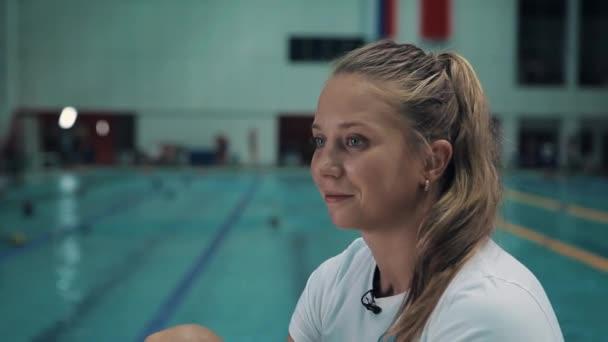 A szép lány a fehér ing előtt sport uszoda mosolyogva ül