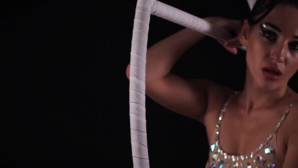 Young female gymnast sitting open mouth on white aerial hoop on black background