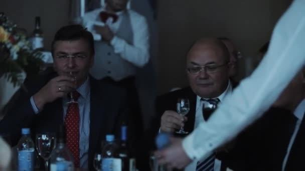 Petrohrad, Rusko - 10. prosince 2016: Podnikatelé v brýlích u stolu banket, pít panáky vodky a vína