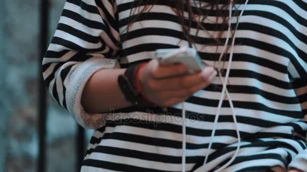 Dívka s dredy a pruhované tričko používat smartphone se sluchátky v uličce