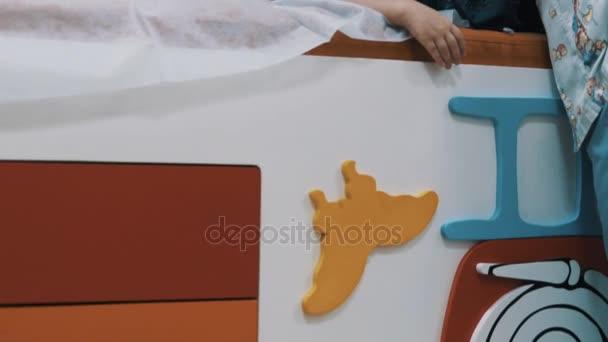 Weibliche Kinderarzt Massagen Brust des kleinen Jungen während der Umfrage auf Couch liegen