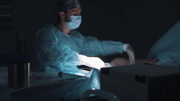 Doctor s using ultrasonography over unconcious surgeon patient leg
