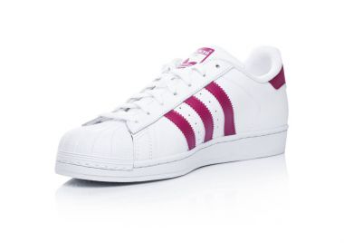 LONDON, UK - JANUARY 12, 2018: Adidas Originals Superstar red shoes on white.German multinational corporation that designs and manufactures sports shoes, clothing and accessories.