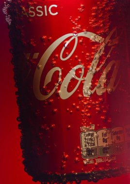 LONDON, UK - JANUARY 02, 2018: Aluminium can of Coca Cola drink inside cola glass container. The drink is produced and manufactured by The Coca-Cola Company.