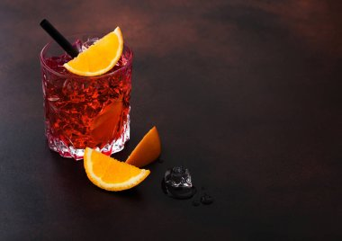 Negroni cocktail in crystal glass with orange slice and black straw on brown table background. Macro