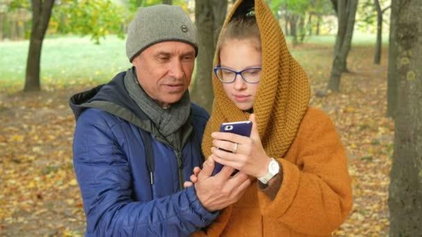 Dcera a otec mluví po telefonu v podzimním parku na videu. Táta se usmívá a směje se její dcera v pubertě. šťastný rodinný koncept