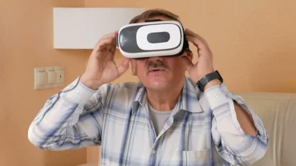 Starší muž s knírkem sedí s virtuální realitou helmu na gauči doma. On se diví, co vidí a snažit se dotknout rukou na virtuální zboží